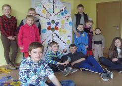 Vaikai fotografuojasi prie pabaigto bendro darbo
