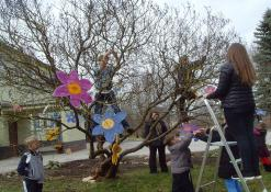 Vaikai puošia medelį popierinėmis gėlėmis