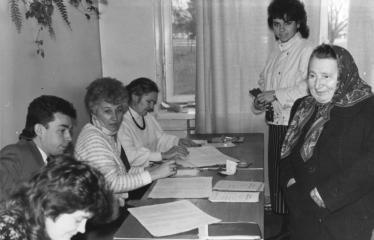 Rinkimai į SSSR liaudies deputatus - Elmos rinkiminė komisija (Naujieji Elmininkai) - Komisijos nariai (prie stalo): Diana Šermukšnienė, Vidmantas Rudokas, Anelė Mackonienė, Milda Garnelienė. Rinkėjai: Lijana Varnienė su močiute Emilija Dūdiene.