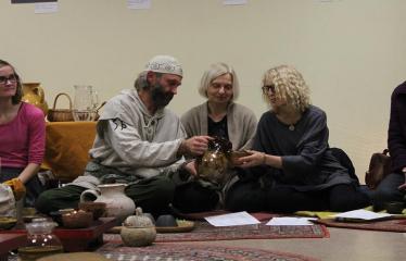 Sutartinių ir arbatos magija - Ramūnas Daugelavičius pilsto renginio svečiams arbatą