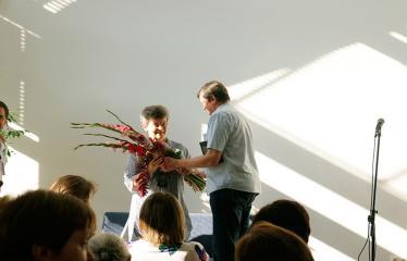 """Festivalis """"Purpurinis vakaras"""" (2018) - Susitikimas su poete Dalia SAUKAITYTE ir jos kūrybos rinktinės """"Purpurinis vakaras"""" sutiktuvės - Gėlės Daliai Saukaitytei nuo seimo nario Sergejaus Jovaišos"""