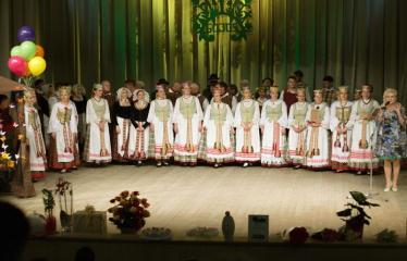 """Šventinis koncertas """"Ošimas…"""" - Liaudiškų šokių kolektyvas """"GOJUS"""", prie mikrofono kolektyvo vadovė Jūratė Uselienė"""